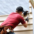 Enhancing his new home first time buyer works to install siding on he is hammering into place a sheet of siding he has on a red Stock Image