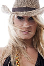 Enigmatic woman with windblown hair long blond wearing a trendy straw hat looking intently at the camera Royalty Free Stock Photo