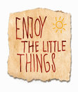 Enjoy the lttle things an inspirational saying handwritten on a torn fragment of textured grunge paper with a sunburst in Royalty Free Stock Images