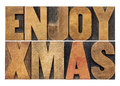 Enjoy xmas christmas greetings or wishes isolated text in vintage letterpress wood type blocks Stock Photos