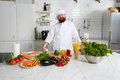 Enjoyable smiling chef with fresh vegetables on big table standing in the kitchen Royalty Free Stock Photo
