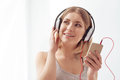 Enjoying amazing music on the weekend musical escape young smiling woman listening to and looking thoughtful while holding her Royalty Free Stock Image