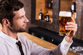 Enjoying the best beer ever side view of handsome young man in shirt and tie examining glass with and smiling while sitting at bar Stock Image