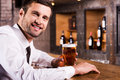Enjoying cold and fresh beer side view of handsome young man in shirt tie holding glass with smiling while sitting at the bar Royalty Free Stock Image
