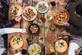 Enjoying dinner together top view of four people having while sitting at the rustic wooden table Royalty Free Stock Photos