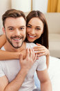 Enjoying every minute together beautiful young loving couple bonding to each other and smiling while sitting in bed Royalty Free Stock Photos