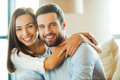 Enjoying every minute together beautiful young loving couple sitting on the couch while women embracing her boyfriend and smiling Royalty Free Stock Photography