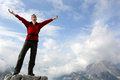 Enjoying freedom in the mountains young mountaineer standing on a rock and Royalty Free Stock Images