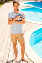 Enjoying his summer vacation full length of handsome young man in polo shirt standing by the pool and smiling to you Stock Image