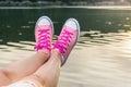 Enjoying by lake. Woman wearing pink sneakers