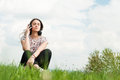 Enjoying music concept with young female sitting outside with ea earphones and relaxing on meadow copyspace Stock Photography