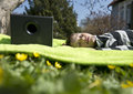 Enjoying music from wireless and portable speakers young boy laying on a blanket in the grass listening to streaming frpm his Stock Photos