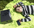 Enjoying music from wireless and portable speakers young boy laying on a blanket in the grass listening to streaming frpm his Royalty Free Stock Image