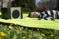 Enjoying music from wireless and portable speakers young boy laying on a blanket in the grass listening to streaming frpm his Royalty Free Stock Images