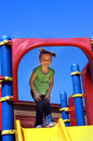 Enjoying recess little girl enjoys time on the playground equipment she is standing inside a large blue metal loop attached to a Royalty Free Stock Photos