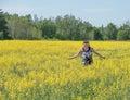 Enjoying a simple walk woman full of youth and vigor through yellow canola farm field Stock Photography