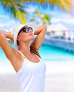 Enjoying summer vacation portrait of pretty girl with hands behind head sunlight tanning on tropical beach luxury spa resort Stock Photography