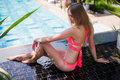 Enjoying suntan. Pretty young woman in bikini sitting near swimming pool. Royalty Free Stock Photo
