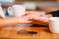 Enjoying their closeness close up of couple holding hands while fresh coffee in cafe together Stock Photos