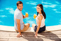 Enjoying their summer vacation top view of happy couple in casual wear holding glasses with orange juice and smiling while sitting Royalty Free Stock Photos