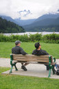 Enjoying the view two guys sitting on a bench at cleveland dam overlooking mountains of british columbia Royalty Free Stock Images