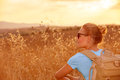Enjoying wheat field in sunset beautiful traveler girl golden light beautiful summer nature farmland europe travel and tourism Royalty Free Stock Photography