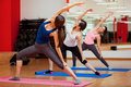 Enjoying yoga class in a gym gorgeous young women practicing and performing an extended side angle pose Royalty Free Stock Photos