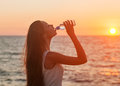 Enjoyment free happy woman enjoying sunset asian caucasian female model drinking from a water bottle at Royalty Free Stock Images