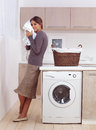 Enjoys a smell of the washed things woman in laundry room Royalty Free Stock Photography