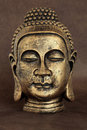 Enlightened one golden buddha head statue over brown lokta natural paper Royalty Free Stock Photography
