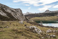 Enol lake in the mountains high mountain landscape with you can see snow background a cloudy day and some roads Royalty Free Stock Image