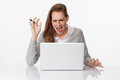 Enraged 20s woman typing on laptop on sparse white desk Royalty Free Stock Photo