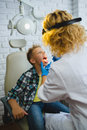 Ent doctor or Otolaryngologist examining a kid throat Royalty Free Stock Photo