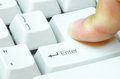 Enter desktop finger pressing the key of the white computer keyboard Stock Image
