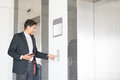 Enter elevator young indian businessman pressing on button waiting door open to inside the lift Stock Photos