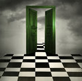 Enter surreal imagine with a green opened door chessboard floor and cloudy sky in the background Stock Image