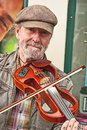 Entertainer at whitby playing an unusual fiddle beside the harbour in east yorkshire Royalty Free Stock Images
