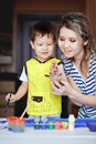 Entertaining childhood, a little boy playing with his mother, draws, paints on the palms. Royalty Free Stock Photo