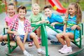 Entertainment for kids image of joyful friends having fun on carousel outdoors Stock Image