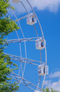 Entertainment observing wheel amusement park behind trees on blue sky background Stock Image