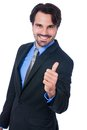 Enthusiastic businessman giving a thumbs up handsome gesture of approval and success as he looks at the camera with beaming Royalty Free Stock Photography