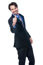 Enthusiastic businessman giving a thumbs up handsome gesture of approval and success as he looks at the camera with beaming Stock Images