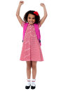Enthusiastic elementary school girl posing with arms raised up victorious Royalty Free Stock Photos