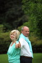 Enthusiastic senior couple giving a thumbs up stylish standing back to back in the garden of approval Stock Images