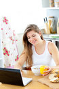 Enthusiastic woman using laptop during breakfast Stock Photo