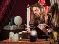 Enticing fortune teller man with tarot cards and crystal ball Royalty Free Stock Photos