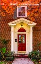 Entrance to brick house with pillars for porch and red door with autum leaves on sidewalk and colorful branches framing picture - Royalty Free Stock Photo