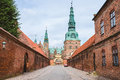 Entrance to Frederiksborg castle in Copenhagen, Denmark - September, 24th, 2015. Red brick fortress wall and green copper spiels o Royalty Free Stock Photo