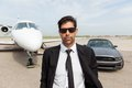 Entrepreneur in front of car and private jet portrait confident male Stock Images