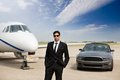 Entrepreneur standing in front of car and private portrait confident male jet at terminal Royalty Free Stock Photos